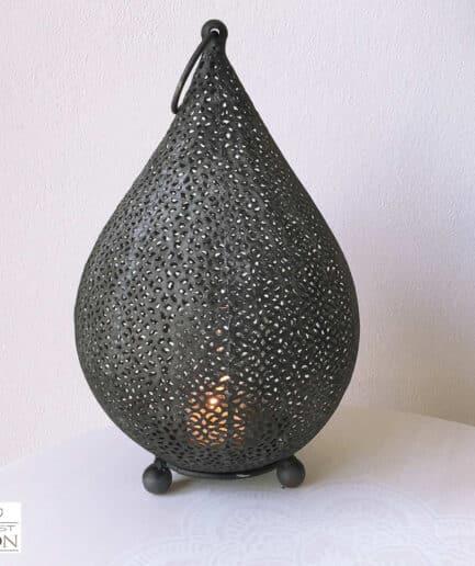 Orientalisches Windlicht aus Schwarzem Metall in Tropfenform. Das Windlicht wirft durch sein Lochmuster ein Schattenspiel an die Wand. In die marokkanische Laterne passt eine Kerze