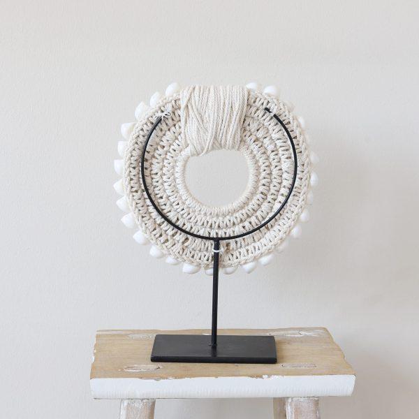 Dekoration aus weißen Muscheln. Muschelkette als Wohndeko Accessoire. Die weiße Muschelkette aus Neuguinea wird auf einem schwarzen Ständer aus Metall präsentiert.