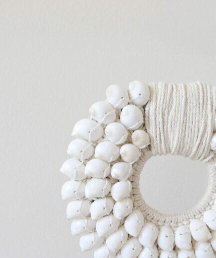 Dekoration aus weißen Muscheln. Tribal Art Muschelkette aus Neuguinea als Wohndeko Accessoire. Das Wohnaccessoire im Boho Stil wird auf einem Ständer präsentiert
