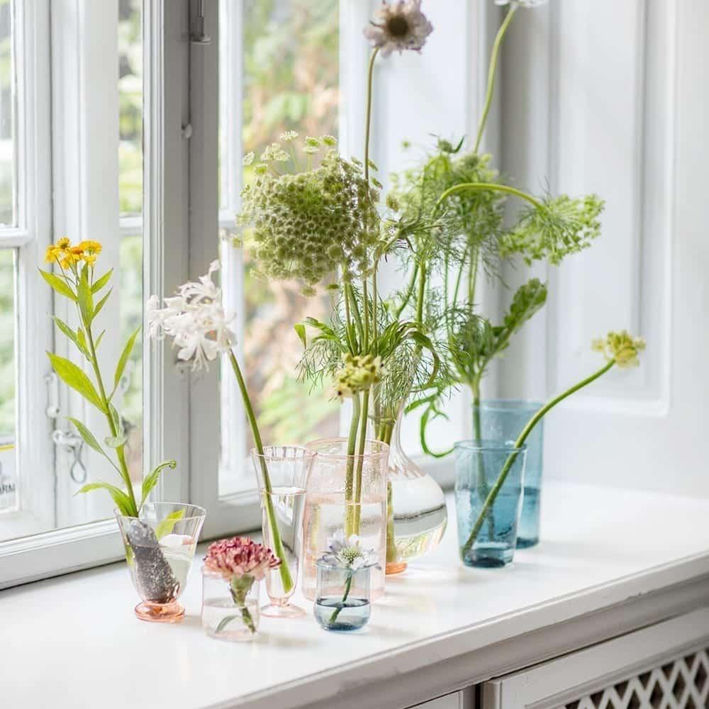 Frühlingsblumen am Fenster in skandinavischen Vasen aus farbigem Glas