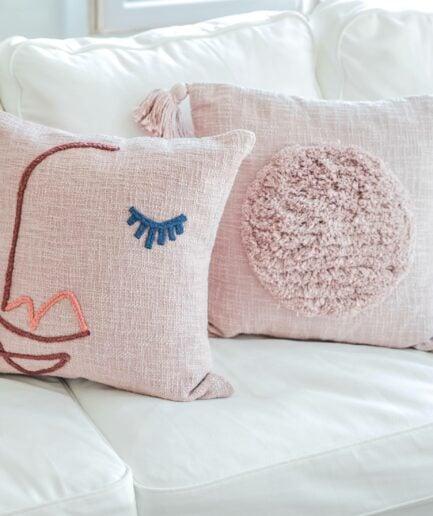 Quadratisches Deko Kissen mit Gesicht in 45x45 cm aus Bio Baumwolle von der Marke Liv Interior. Rosa Sofakissen im skandinavischen Design. Wohndeko im Soulbirdee Onlineshop