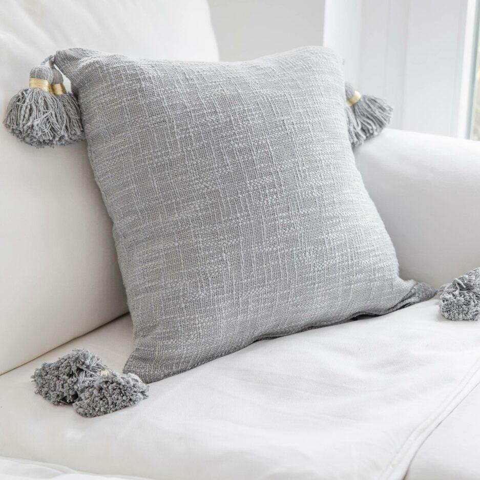 Deko Kissen-Bezug in Grau oder Rosa mit süßen Bommeln von der Marke Liv Interior | 45 x 45 cm aus Bio Baumwolle. Deko Kissen für das Sofa