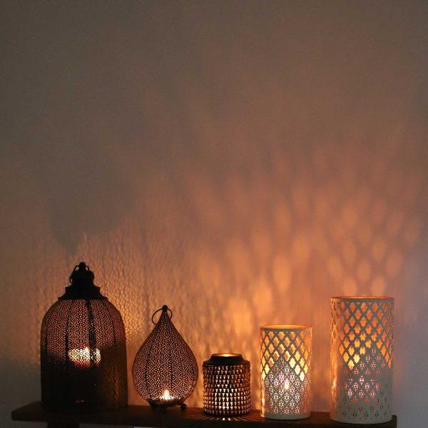Marokkanische Windlichter aus Metall in Schwarz oder Gold und Weiss. Die Laternen bieten Platz für Kerzen und haben verschiedene Muster durch die das Kerzenlicht scheint