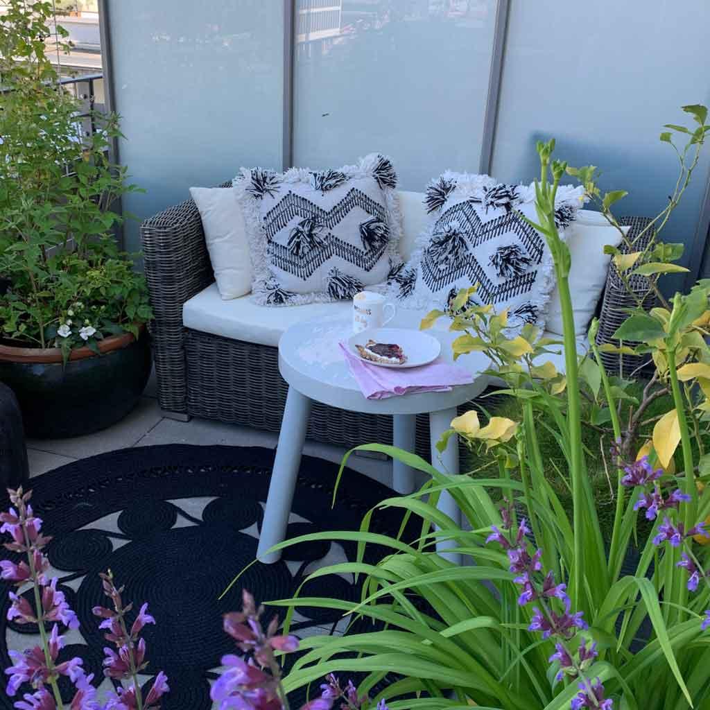 Outdoor Deko mit Teppich und Kissen und Licht. Teppiche für draußen aus wetterfestem PET & weiche Kissen & Windlicht & Lampe | Outdoor Teppich im Boho Stil