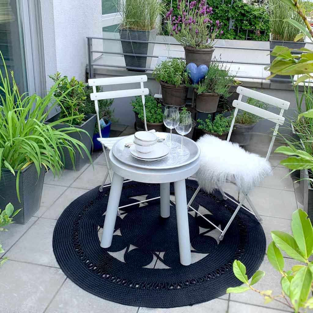 Runder Outdoor Teppich in Mandala Form aus weichem PET für den Balkon und die Terrasse. Dazu Kissen im Boho Stil und im skandinavischen Stil. Boho Teppich für draußen in Schwarz
