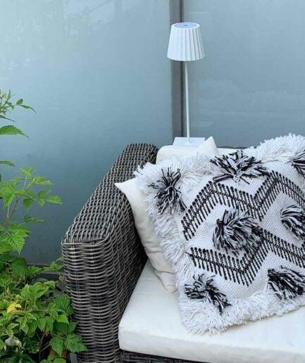 Outdoor Deko mit Teppich und Leseleuchte für den Balkon und die Terrasse. Dazu passende Kissen im Boho Stil und im skandinavischen Stil. Outdoor Lampe mit Akku ohne Kabel